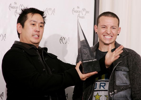 "LOS ANGELES - NOVEMBER 14:  Musicians Joe Hahn (L) and Chester Bennington of Linkin Park pose with theor award in the press room before being removed by security at the 32nd Annual ""American Music Awards"" at the Shrine Auditorium November 14, 2004 in Los Angeles, California. (Photo by Carlo Allegri/Getty Images)"