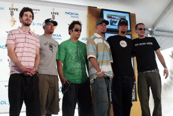 "PHILADELPHIA - JULY 02:  (L to R) Guitarist Brad Delson, bassist Dave ""Phoenix"" Farrell, DJ Joe Hahn, singer Mike Shinoda, drummer Rob Bourdon, and singer Chester Bennington of Linkin Park speak backstage at ""Live 8 Philadelphia"" at the Philadelphia Museum of Art July 2, 2005 in Philadelphia, Pennsylvania. The free concert is one of ten simultaneous international gigs including London, Berlin, Rome, Paris, Barrie, Tokyo, Cornwall, Moscow and Johannesburg. The concerts precede the G8 summit (July 6-8) to raising awareness for MAKEpovertyHISTORY.  (Photo by Peter Kramer/Getty Images)"