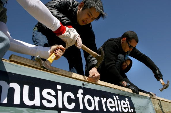 NEW ORLEANS - FEBRUARY 27: Joe Hahn (L) and Chester Bennington (R) of the band Linkin Park use hammers to nail frames together as they work with Music for Relief and Habitat for Humanity while rebuilding homes affected by Hurricane Katrina on February 27, 2008 in New Orleans, Louisiana.(Photo by Sean Gardner/Getty Images)
