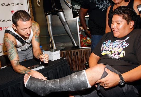 LAS VEGAS - JULY 04:  Linkin Park singer Chester Bennington signs a cast for Brandon Saliego of Arizona during the grand opening of Club Tattoo inside the Miracle Mile Shops at the Planet Hollywood Resort & Casino July 4, 2009 in Las Vegas, Nevada. Bennington is a co-owner of the tattoo parlor.  (Photo by Ethan Miller/Getty Images)